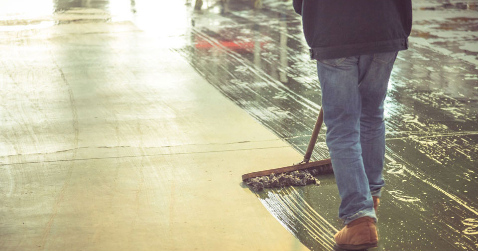 Worker mopping concrete
